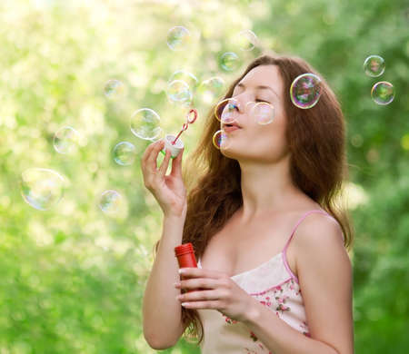 Young beautiful girl blowing bubbles in the park on green background photo