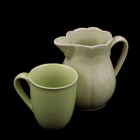 Old green ceramic pitcher and cup isolated on black background photo
