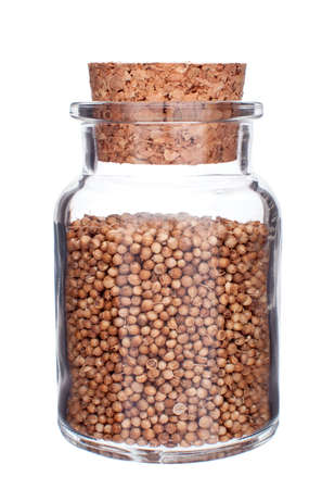 closed corks: glass bottle full of coriander seeds isolated on white background