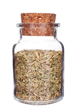 dill seed: glass bottle full of fennel seeds isolated on white background