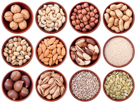 assortment of nuts and seeds in ceramic bowls isolated on white background photo