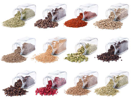 Spices and herbs are scattered on a white background from glass bottles photo
