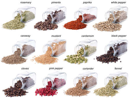 pimento: Spices and herbs are scattered on a white background from glass bottles. Lables Stock Photo