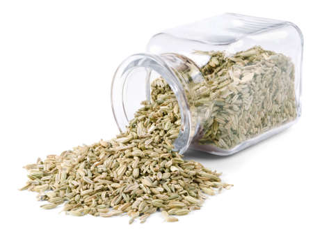 Fennel seeds is scattered on a white background from glass bottle