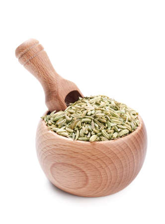 fennel seed: Wooden scoop in bowl full of fennel isolated on white background