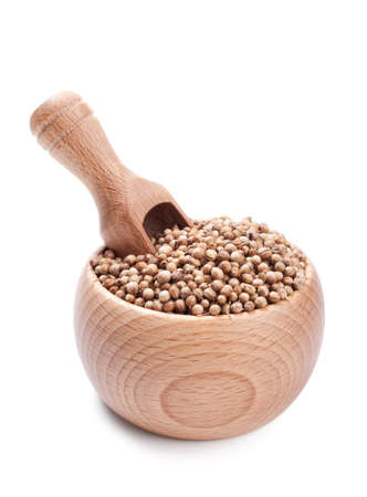 Wooden scoop in bowl full of coriander seeds isolated on white background Stock Photo - 12783284