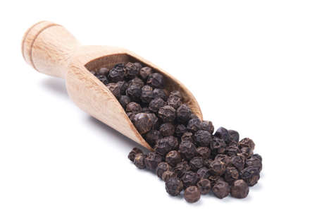 black peppercorn: Wooden shovel with black peppercorn scattered from it
