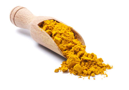 Wooden shovel with dry turmeric scattered from it