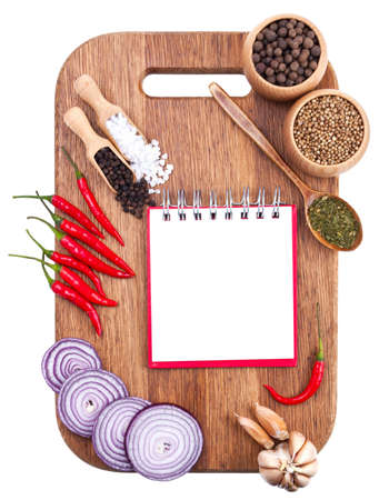 Open notebook and fresh vegetables on an old wooden cutting board  Isolated on white photo
