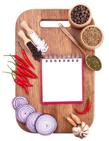 kulinarne: Otwórz notatnik i świeże warzywa na starej płycie drewnianej cięcia na białym
