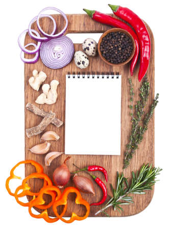 Open notebook and fresh vegetables on an old wooden cutting board  Isolated on white Stock Photo