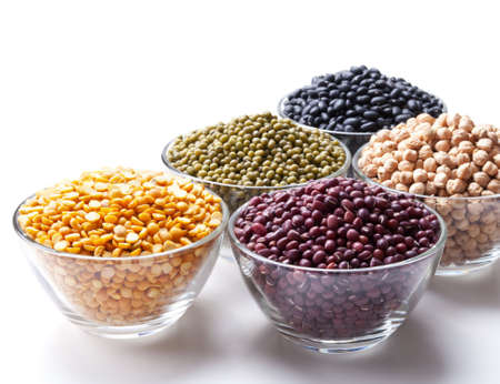 glass bowls with legumes on white background