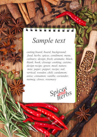 Open notebook with spices and herbs on the old wooden cutting board