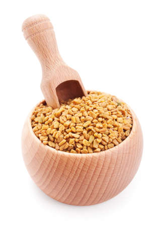 Wooden scoop in bowl full of fenugreek isolated on white background Stock Photo - 15531903