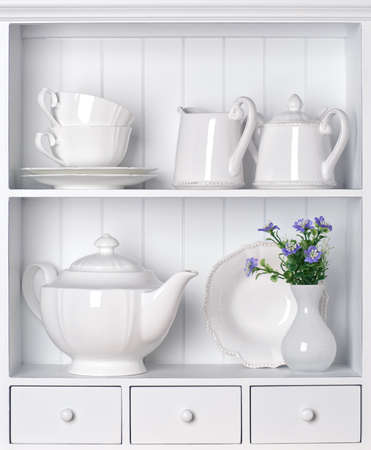 White shelf with vintage porcelain tableware photo