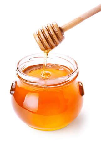 Glass jar of honey with wooden drizzler isolated on white background Standard-Bild