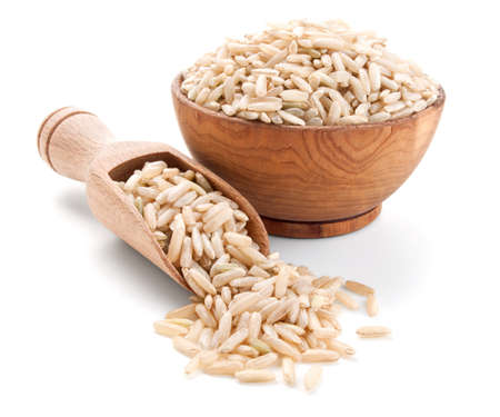 unpolished: unpolished rice in a wooden bowl isolated on white background Stock Photo