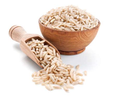 arroz: arroz moreno en un taz�n de madera aislada sobre fondo blanco Foto de archivo