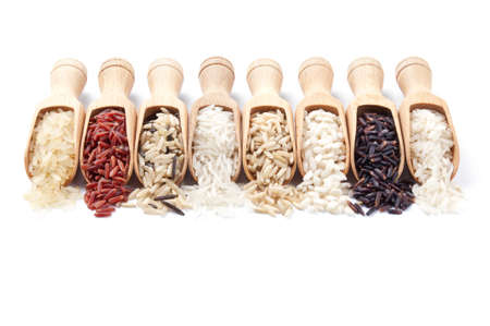 brown rice: Wooden scoops with different rice types scattered from them on white background Stock Photo