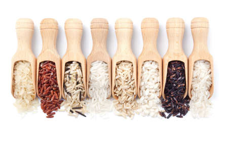 wild rice: Wooden scoops with different rice types scattered from them on white background Stock Photo