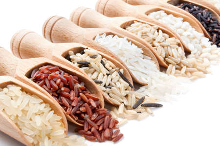 Wooden scoops with different rice types scattered from them on white background Standard-Bild