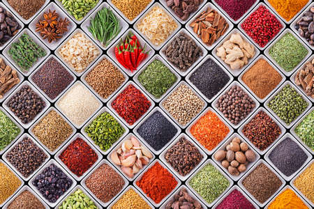 Seamless texture with spices and herbs over black background Фото со стока