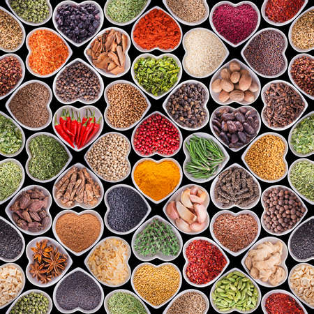 Seamless texture with spices and herbs over black background photo