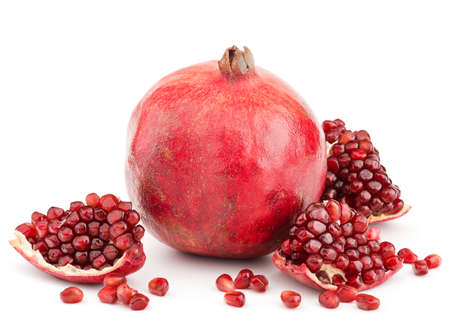 whole pomegranate with pieces and grains isolated on white background