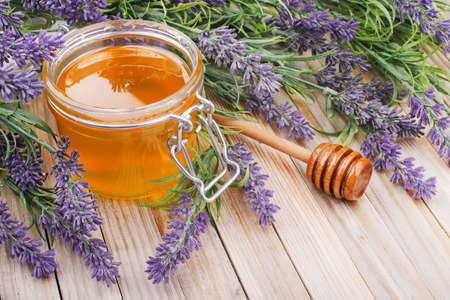 jar of liquid honey with lavender. artificial flowers