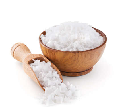 Cyprus sea salt flakes in a wooden bowl isolated on white background