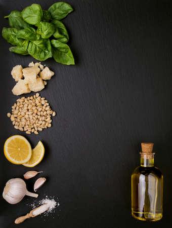 spacing: Ingredients for pesto sauce preparing on black slate background. Top view with free spacing Stock Photo