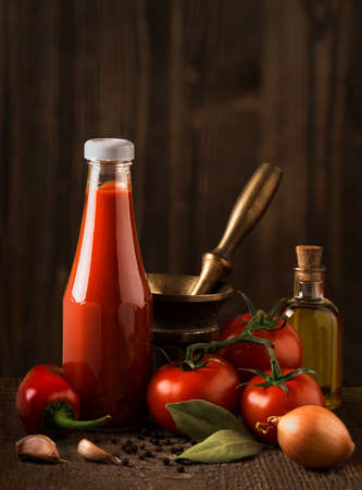 salsa de tomate: Dark still life with ketchup and ingredients on the rough wood. Small depth of field. Blurred background.