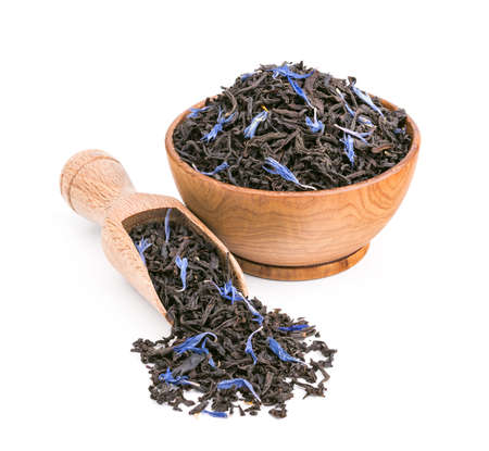 blue petals: Black tea with blue petals in a wooden bowl isolated on white background