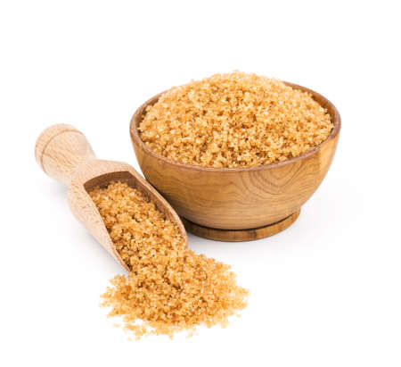 brown cane sugar in a wooden bowl isolated on white background