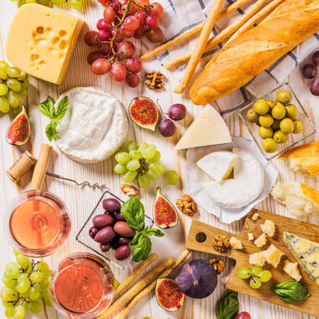 appetizers: An abundance of cheese, fruits, breads, wine and snacks on white rustic table from above. French appetizer background