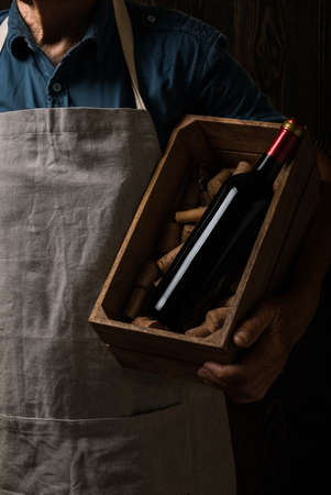 Old winemaker holding a wooden box with bottle of red wine. Composition in dark colors