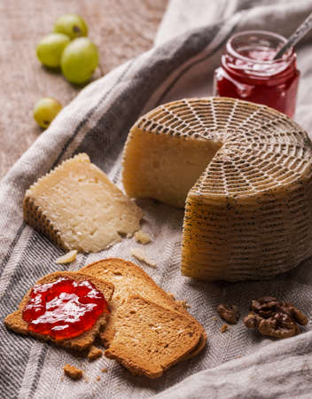 tabla de quesos: Still life with goat cheese, bread slices and jam. Rustic style