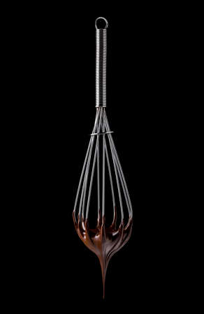 Whisk with melted chocolate cream isolated on black