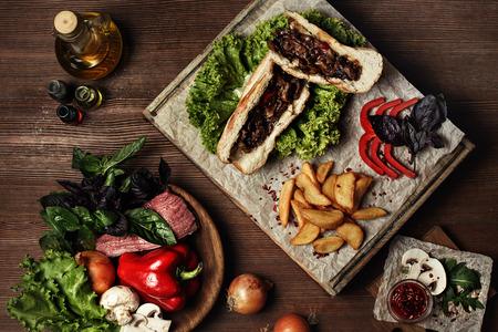 Accueil hamburgers faits avec des frites, tomates cerises et sauce barbecue servi sur plaque de bois Banque d'images - 51832439