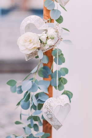 nicely: Wooden beam nicely decorated with white roses and laced hearts close up.