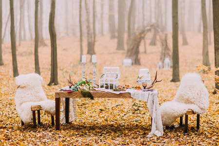 Dreamlike wedding table decorated in scandinavian style in the autumn forest. Stock Photo