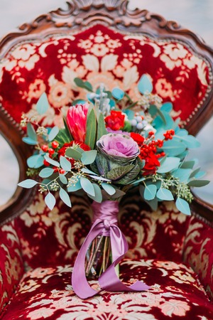 skillfully: Skillfully decorated wedding bouquet on the red vintage armchair.