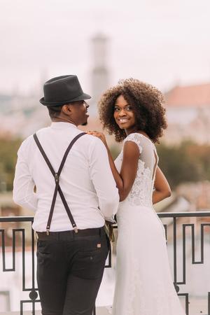 Belle mariée africaine et le marié élégant chapeau tenant les mains sur le toit. Banque d'images - 53004988