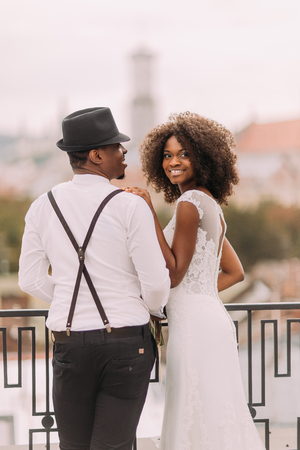 Beautiful african bride and stylish groom in hat holding hands on the rooftop. Standard-Bild