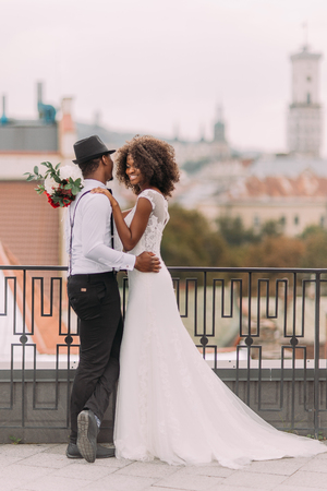 adoring: Lovely african newlyweds softly holding each other and smilling. Rooftop. Ancient Lviv architecture on background. Stock Photo