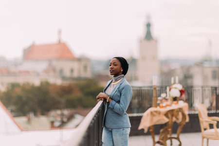 wonderfull: Beautiful african girl enjoys the view of wonderfull Lviv architecture standing on the rooftop. Stock Photo