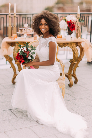 Happy young black bride smiling with bouquet of red flowers and sitting on vintage terracotta chair.