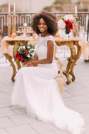 diamante negro: Feliz novia joven negro sonriente con el ramo de flores rojas y sentado en la silla de terracota de la vendimia. Foto de archivo