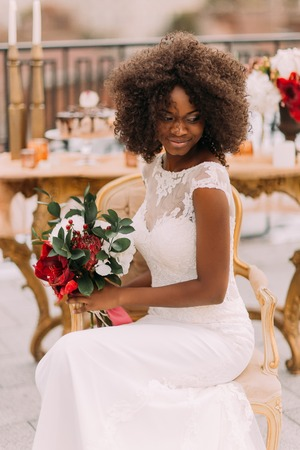 married: Wonderful black bride happily smiling with eyes closed and holding a bouquet of red flowers. Wedding day.