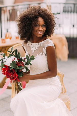 Charming african bride with wedding bouquet in hands cheerfully smiling to the camera. Standard-Bild